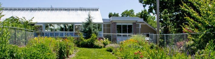 Wide image of outdoor gardens and greenhouse